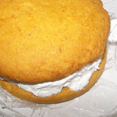 Picture of backed goods, pumpkin whoopie pie with filling.